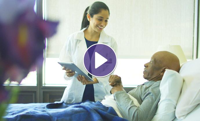 Gumagamit ng tablet ang isang doctor ng VITAShabang nakikipag-usap siya sa isang pasyenteng nasa kama ng ospital