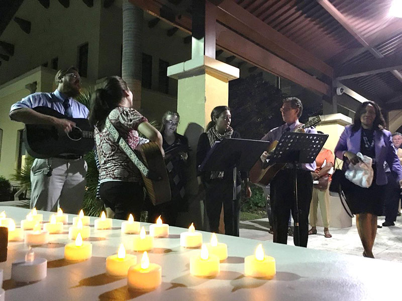 Five music therapists play guitar and sing, with candles in the foreground