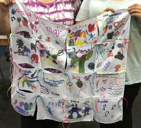 Two children hold up a remembrance quilt they helped to make