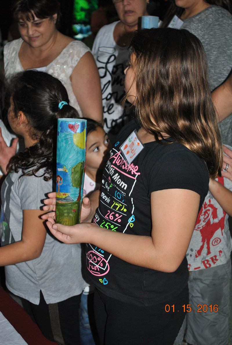 A girl holds a candle with a decorative cover honoring a loved one