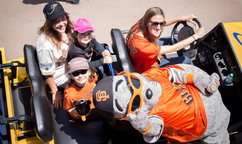 The group sits in a team vehicle with Lou Seal, the Giants mascot