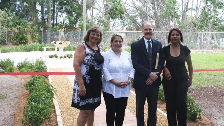 The group poses in front of the ceremonial ribbon at the scatter garden