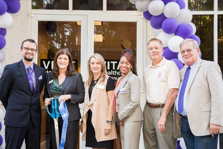 The group posing with the ceremonial scissors and ribbon from the ribbon-cutting