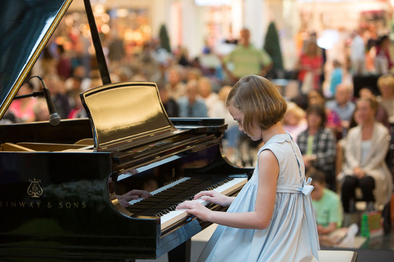 A young girl plays piano