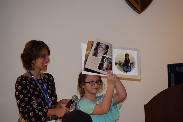 A girl holds up a memory book with photos for the group to see