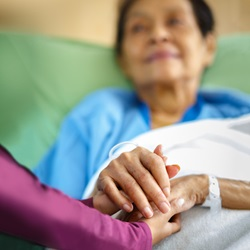 A caregiver holds the hand of a patient who is lying in bed