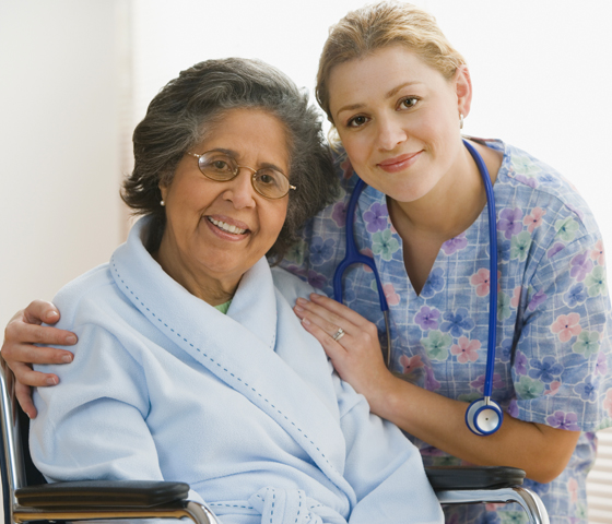 A patient in a wheelchair smiles with a nurse's assistant