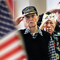 Military veterans salute the flag
