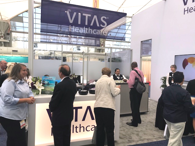 People talk with VITAS team members at the VITAS booth at a conference