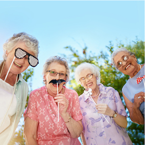 Four senior women smile outside while playing with costume mustaches and glasses