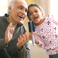 A man and child sing and clap together