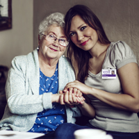 A patient holds hands with a social worker