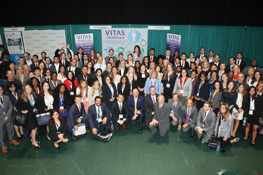 The group gathered for a photo in front of the VITAS booth