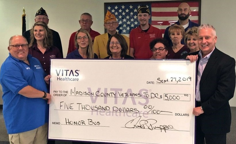 The group shows a large, ceremonial check