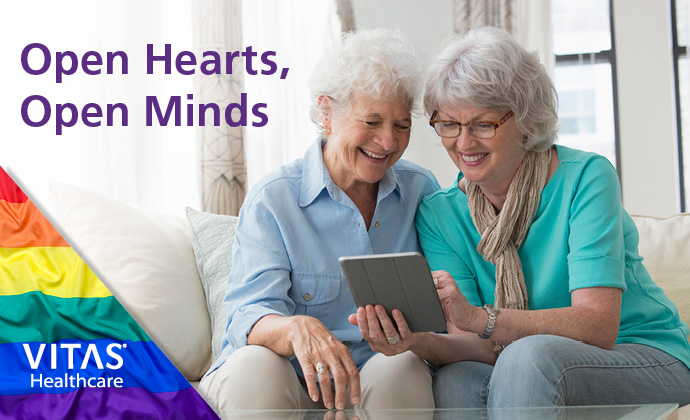 Two smiling, older woman sit together on a sofa and look at a tablet
