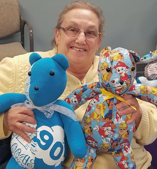 A woman holds two Memory Bears at a Chicago reunion