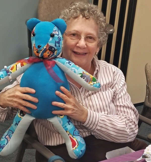 A woman holds a Memory Bear sewn by VITAS volunteers