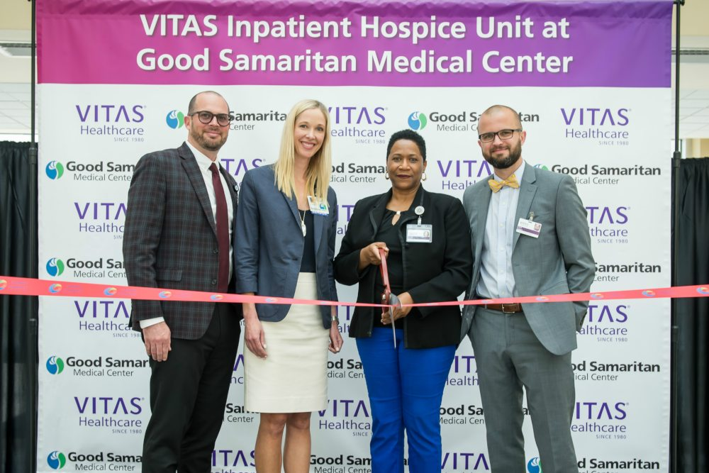 Good Samaritan and VITAS executives stand behind the ribbon with a pair of ceremonial scissors