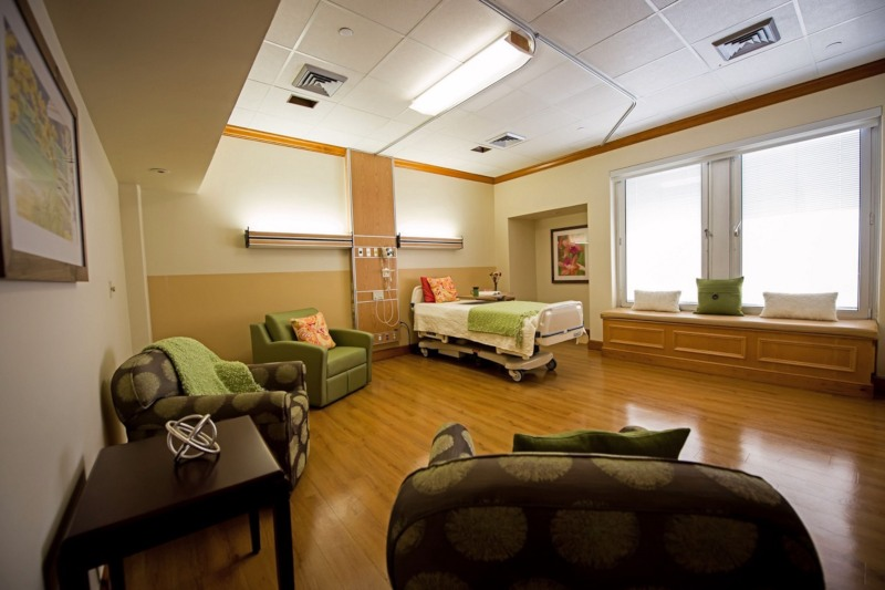 A patient room with a bed, several armchairs and two sunny windows