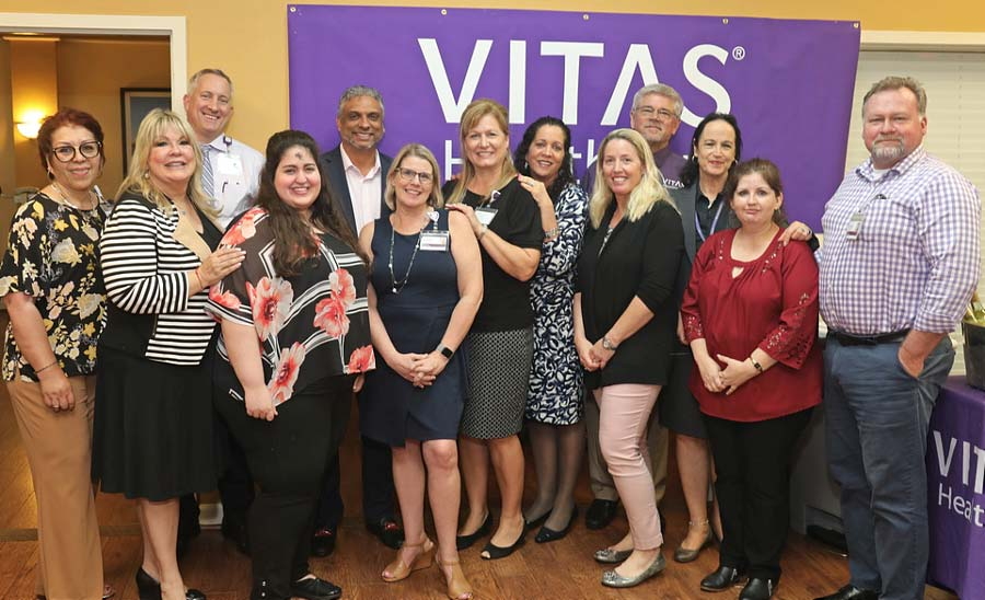 The VITAS team poses for a group photo at the open house in front of a purple VITAS banner