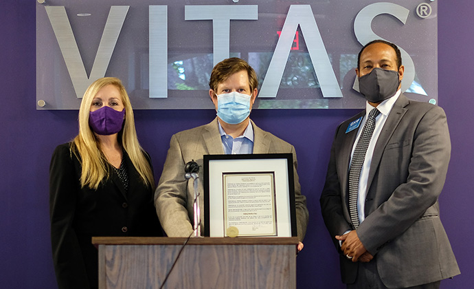 The group stands in front of the VITAS sign with the proclamation