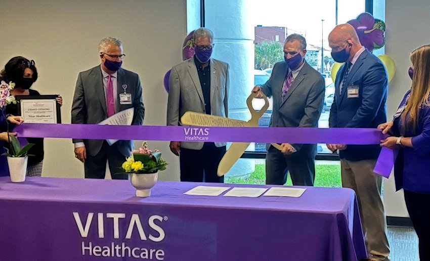 The dignitaries cut a large purple ribbon with ceremonial gold scissors