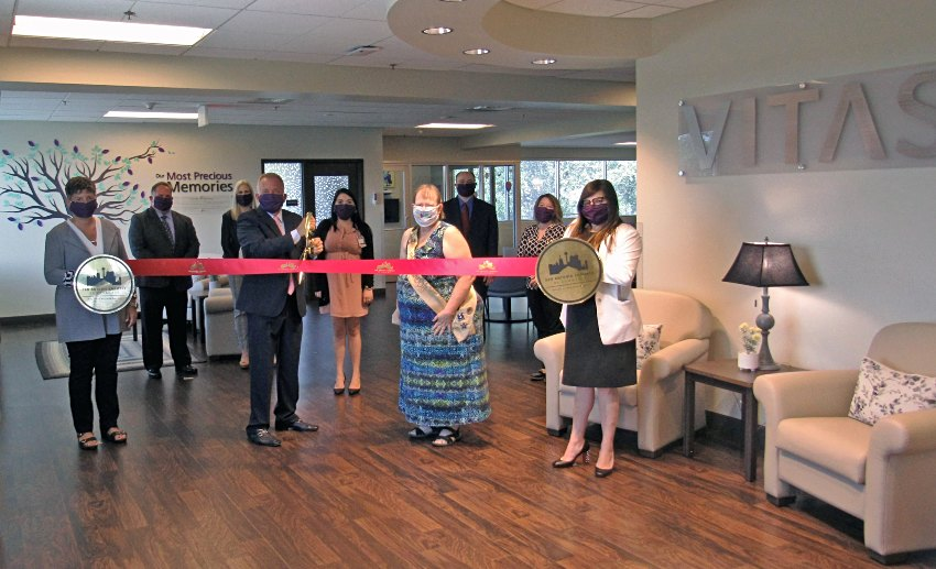 The group holds a ceremonial ribbon for the ribbon-cutting inside the inpatient hospice unit