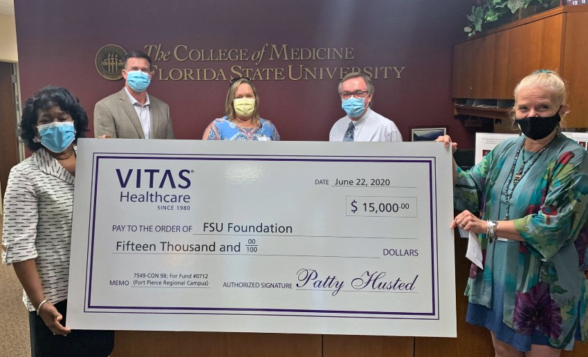 The group holds a large ceremonial check at the FSU College of Medicine offices