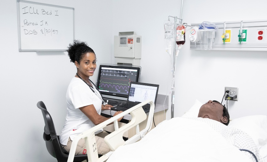 A nursing student sits at a computer near the manikin in a hospital bed