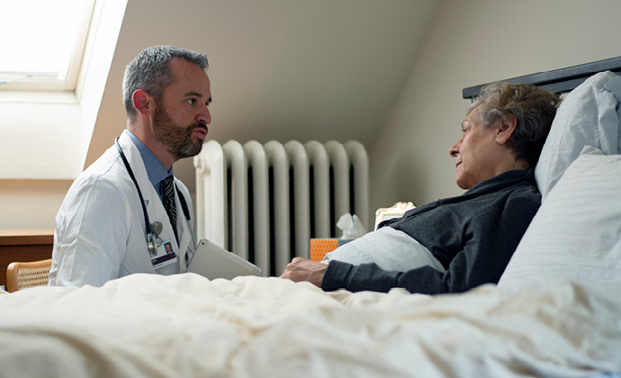 A patient lies in bed at home and talks with a VITAS physician