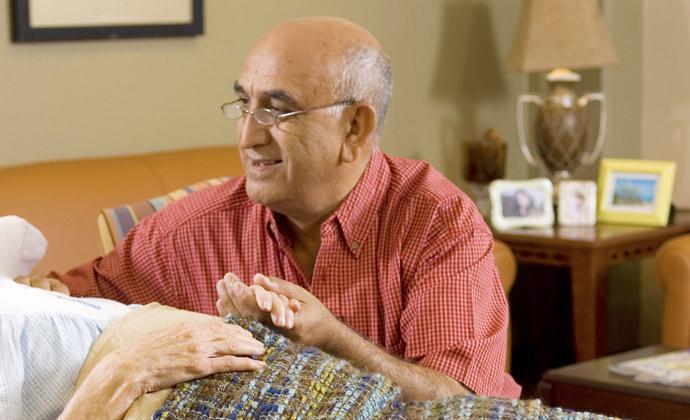 Un hombre sostiene la mano de su esposa mientras ella yace en una cama de hospital