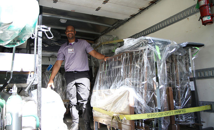 VITAS team member stands in the cargo area of a home medical equipment delivery truck that's loaded with a bed frame
