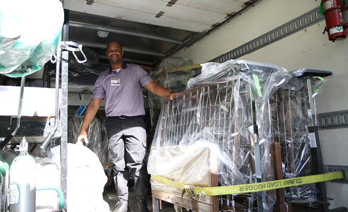 Un miembro del equipo de VITAS está parado en la zona de carga de un camión de reparto de equipos médicos a domicilio que está cargado con la estructura de una cama