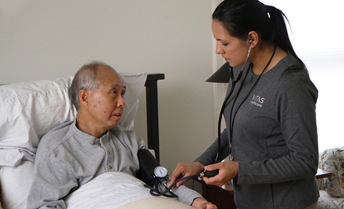 Một y tá kiểm tra áp huyết của người đàn ông khi ông ngồi trên giường ở nhà