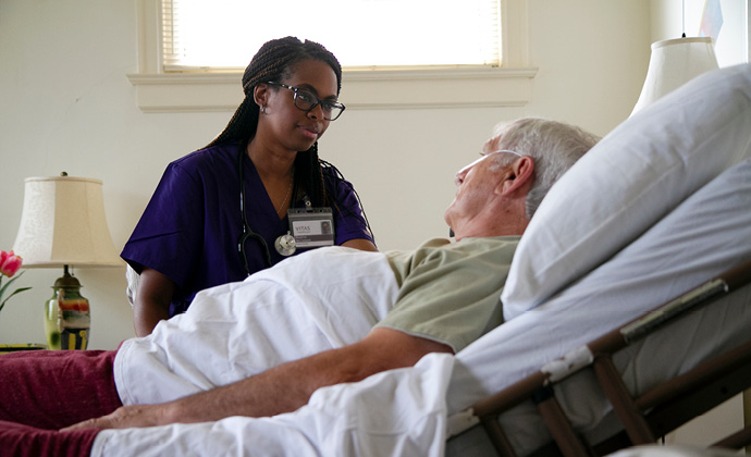A male patient in bed at home talks with a VITAS nurse