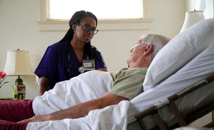 Một bệnh nhân nam ngồi trên giường tại nhà đang nói chuyện với y tá VITAS