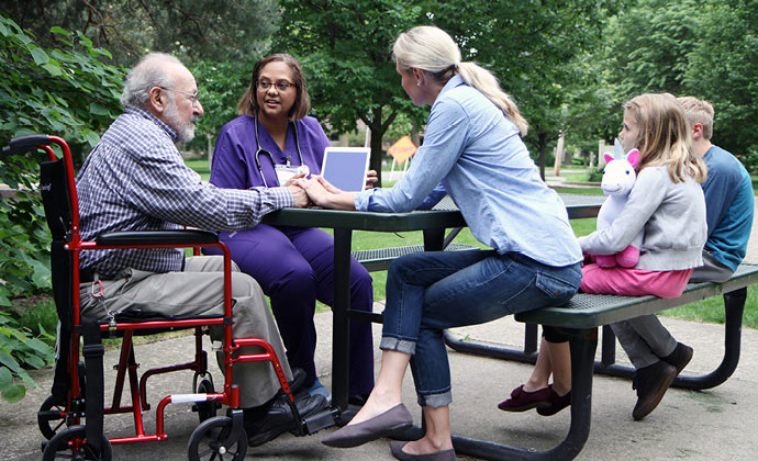 A patient in a wheelchair sits at a picnic table with his relatives and a VITAS team member