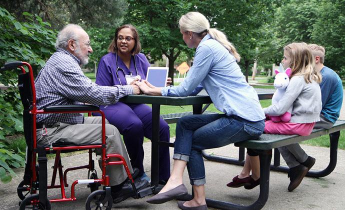 Một bệnh nhân ngồi xe lăn bên bàn ăn ngoài trời với họ hàng và thành viên nhóm VITAS