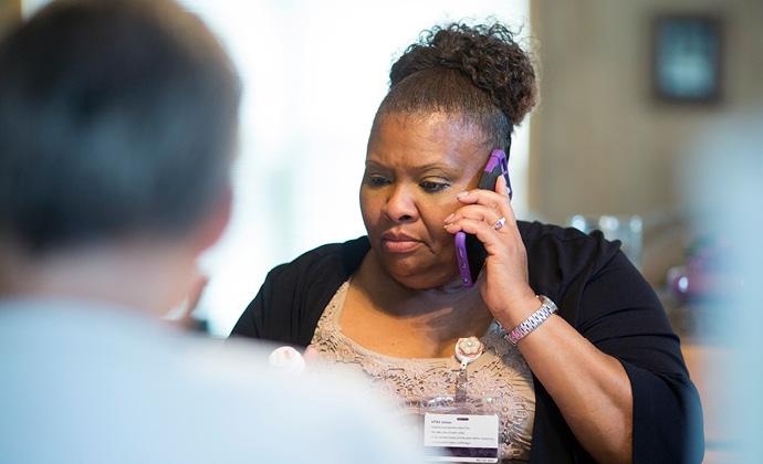 Una miembro del equipo de VITAS escucha con un teléfono celular