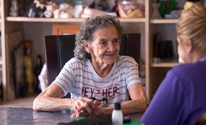 Una paciente y una enfermera de VITAS hablan sentadas en una mesa de la cocina
