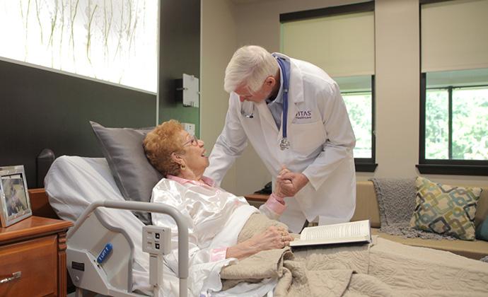 Un médico habla con una mujer acostada en su cama
