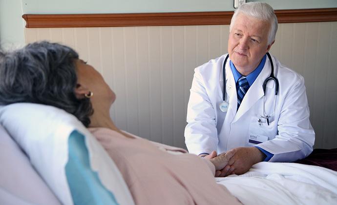 VITAS醫師握著躺在床上的女士的手