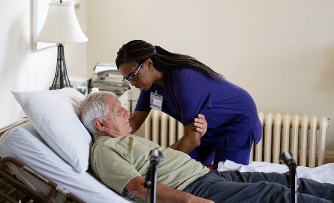 VITAS團隊成員協助病人從床上坐起來