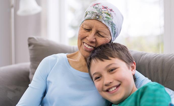 包著頭巾的女士與男孩坐在沙發上彼此依偎