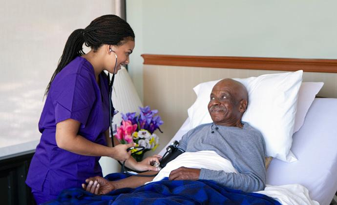 VITAS團隊成員使用聽診器檢查躺在病床上的男士