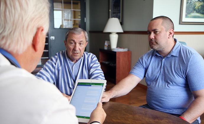 兩位男士坐在桌子前與VITAS醫師談話