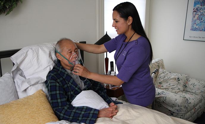 VITAS團隊成員協助坐在病床上的病人戴上氧氣罩