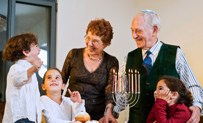 Two grandparents smile with their three grandchildren around a lighted menorah