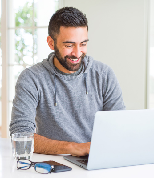 A man smiles as he is working on a laptop