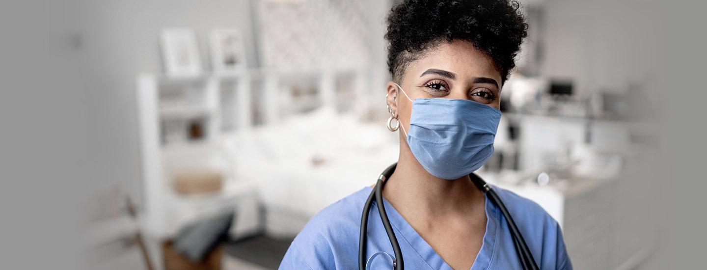 Una enfermera con una mascarilla valora la respiración de un paciente